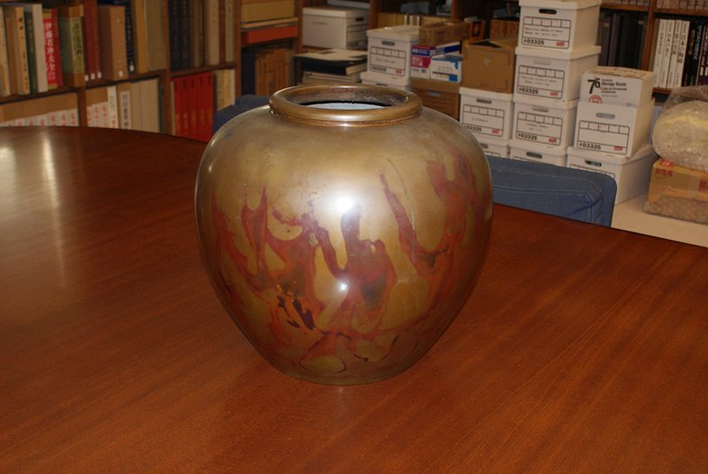 large, bulbous, smooth bronze vase with reddish flame-like markings along sides