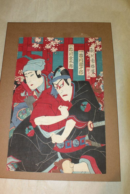 center/right print; two actors in center of image; actor in front wears heavy red eye makeup, black robe with red underneath, a red obi with sword tucked in, and a blue sash around his head; actor in back wears red and blue robe with light blue headdress; print is richly colored with red, black, blue, and teal; white blossoms in background, text in cartouches in URQ