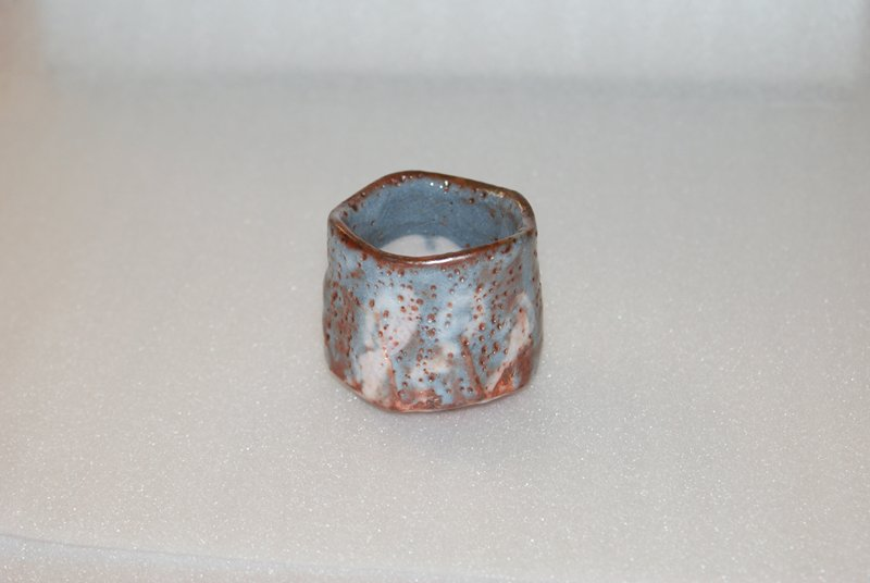 irregularly shaped sake cup with blue and white glaze; many inherent pockmarks