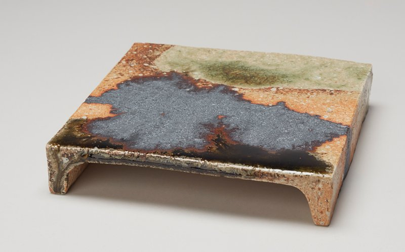 flat square plate with two feet running the length of two sides; reddish-tan base glaze with irregular linear forms in green, dull grey and brown