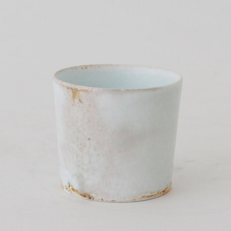 cylindrical white cup with faint celadon and lavender over glaze; simple, clean silhouette