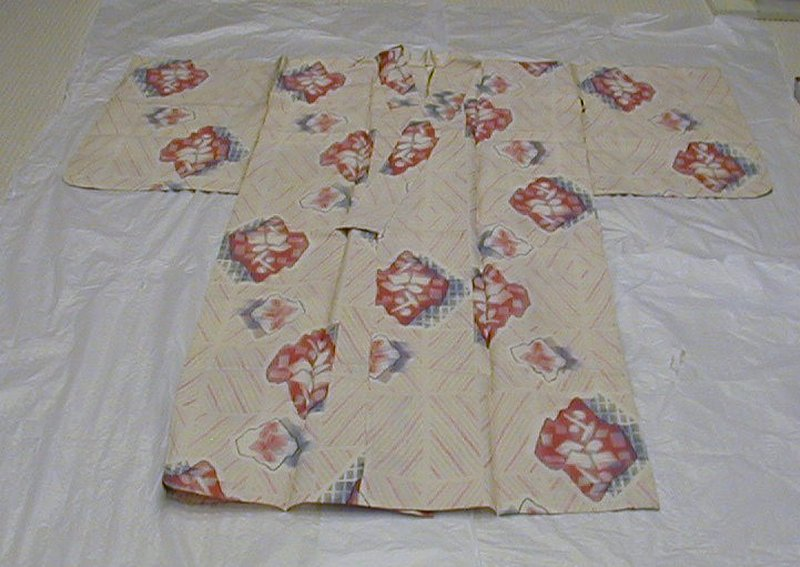 off-white kimono with yellow, gray, and pink spots arranged in diamond pattern in background; larger red diamond motifs throughout with red and blue abstract shapes inside