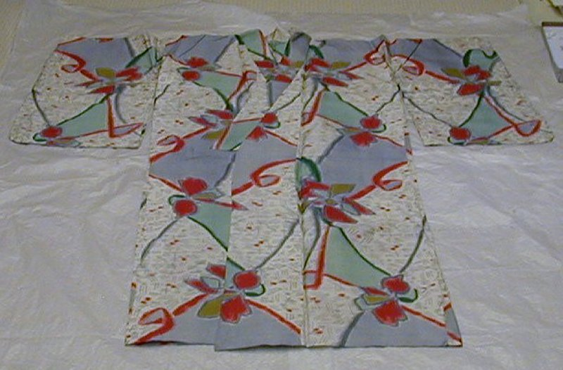 background swaths of gray, green, and white with hash marks; sweeping ribbon designs in red, green, and blue-gray; large flowers with red, green, yellow, and red petals