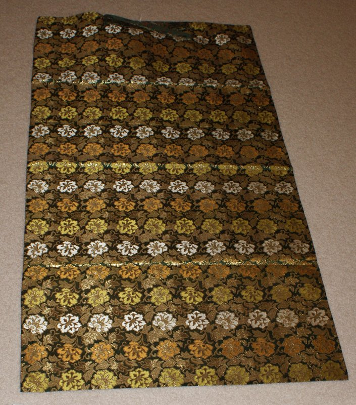 rectangular cloth with tie on one end; dark green background with brocade pattern of flowers in tan, gold, white, and lime green; purple lining