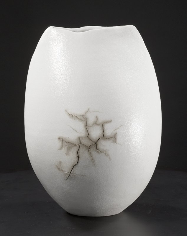 egg-shaped white vessel with flat, uneven top; horizontal slit across top with uneven lips; bulge on both sides near center with network of cracks highlighted in gray