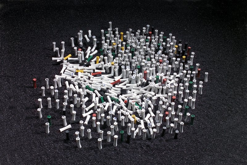 gallery installation piece; 550 total pieces--porcelain chopstick rests with hexagonal cross-sections and slightly tapered centers: unglazed with face drawn on one end in black marker, clear/white glazed with face in blue underglaze on one end, red glazed with white face on one end, green glazed with white face on one end, gold glazed with black face on one end, black glazed with white face (incised in black glaze) on one end; four boxes of black sand; see Notes for inventory break-down