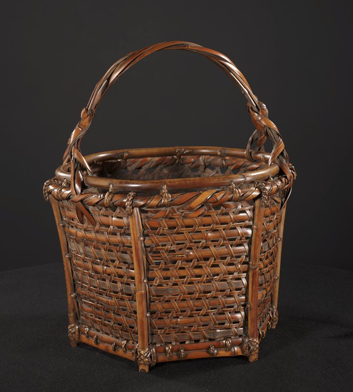 stout, hexagonal basket with inner lip; two crisscrossing handles with ribbon weave near bottom of handle prongs; closed weave with thin bamboo strips crossing wider horizontal strips