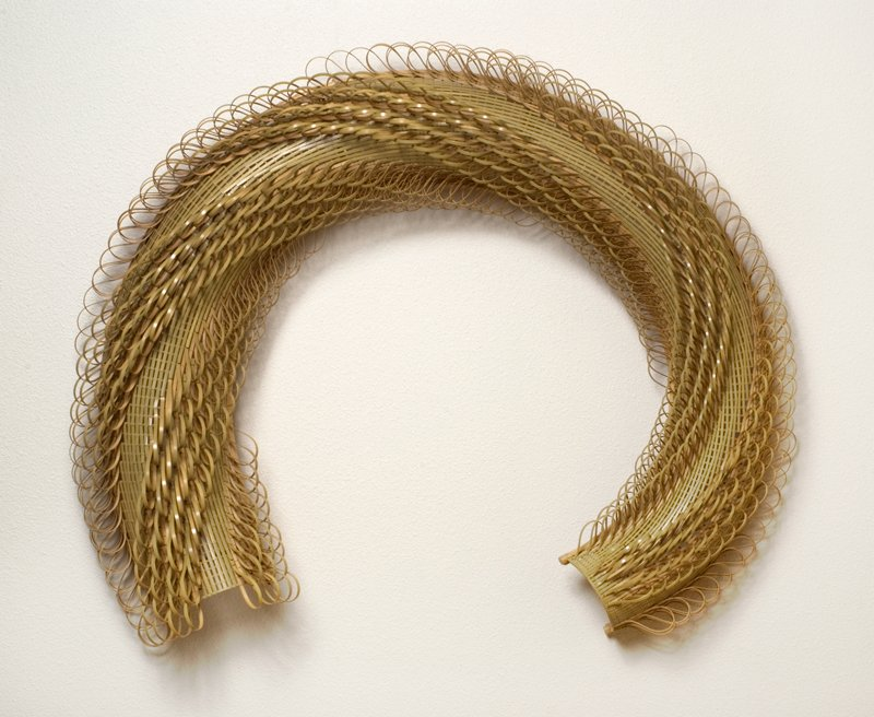 half-circle form with one end slightly tapered; diagonal rows of bamboo loops wind around form