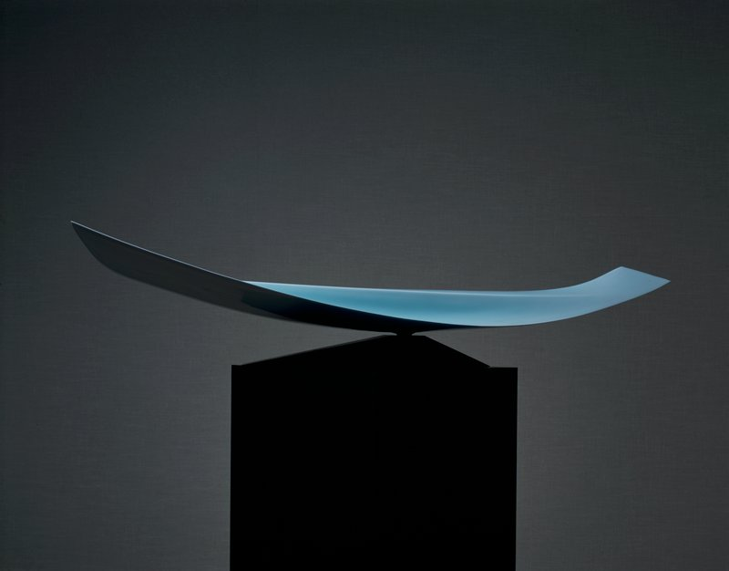 horizontally oriented finlike form that bows upward on both ends; one end dramatically pointed; wider, vertical rise in center; mounted on wooden base