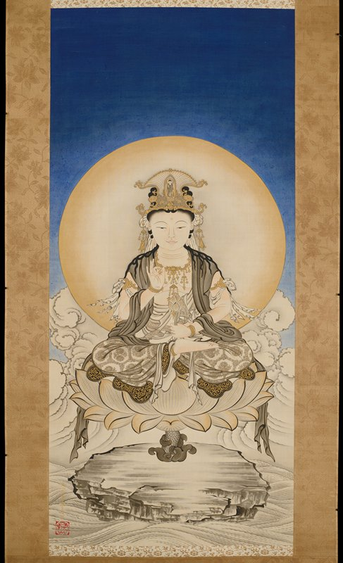 Kannon figure seated on lotus on rock, wave-like motif underneath; in the background is a large gold-bordered halo and cloud-like motif behind; upper half of composition a very deep indigo blue; green and gold mount with lucite roller