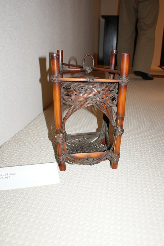 open sided square lantern-shaped basket: four bamboo posts support woven structure with open sides, wide, round opening at top, decorative knots at centers; crisscross woven base; crossing supports with loop for hanging at top; decorative weaving and knots at corners; short, squat bamboo insert for flowers