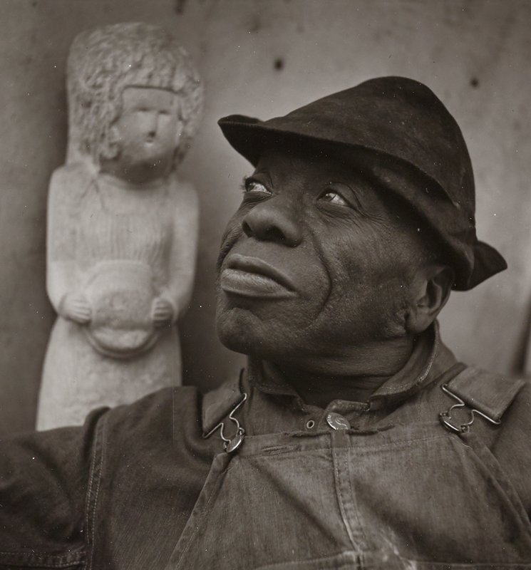 portrait of black man looking up toward ULC; man wears a brimmed cap and overalls; sculpture of a standing figure over man's PR shoulder