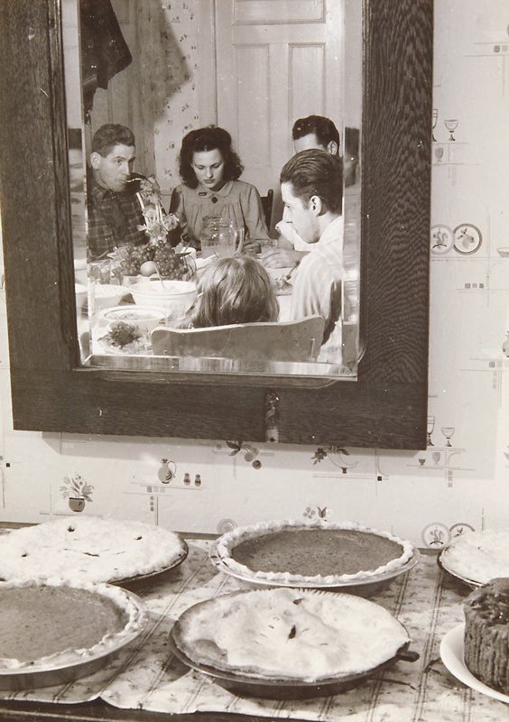 family gathered around a table appear in the reflection of mirror above tabletop filled with assorted pies