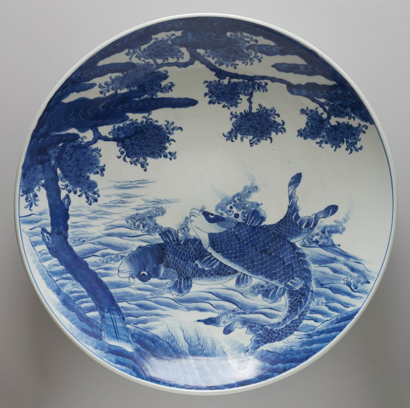 very large dish with wide ring foot; blue and white; decorated with pair of carp jumping out of water beneath a blooming cherry tree; four vignettes with fish on exterior, with dart-like pattern around foot; underglaze cobalt decor on porcelain