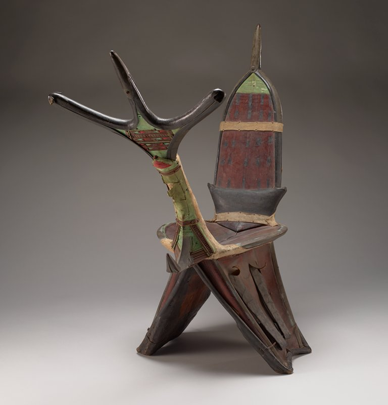 saddle with high front and back; front has three-pronged antler-like motif; bullet-shaped backrest with pointed prong on top; back of backrest and front of front element decorated with cut and appliqued leather and cloth strips forming bands and bars with triangle designs and X's in red, green and brown; applied tan animal hide with short fur on front, back and around bottom of seat; seat and bottom are brown leather with black pigment linear designs
