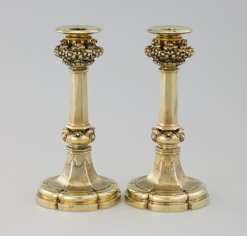 George IV Gothic Revival; six lobes on foot; hexagonal tapered shaft; round rim; bulb above foot has alternating three-dimensional leaves and tiny frogs; three-dimensional collar below candle cup with repeating leaf designs