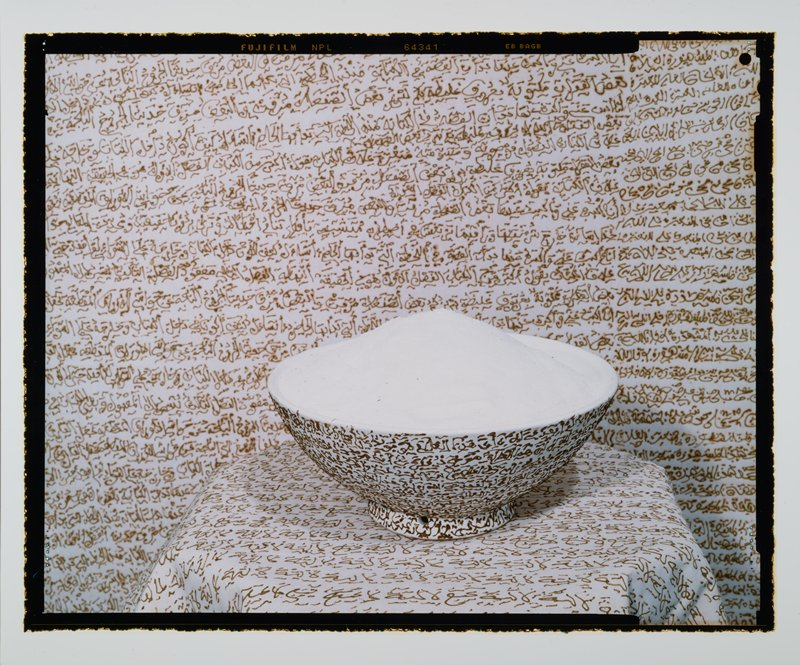 white bowl of sugar on a white ground; bowl and ground have lines of brown text overall