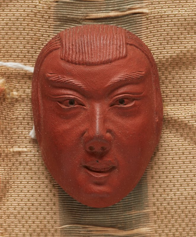 netsuke in the form of a mask; red clay; pleasant looking face of young man with teeth showing behind parted lips; hair over ears and combed forward into bangs; 2013.29.1217.1-6 received attached to patterned orange, cream and blue ribbon (ribbon in poor condition--shredded)