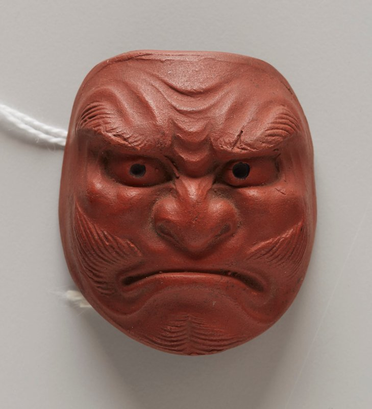 netsuke in the form of a mask; red clay; frowning mouth; wide flat nose; whiskers on chin and sides of mouth; thick eyebrows; furrowed brow; beady eyes