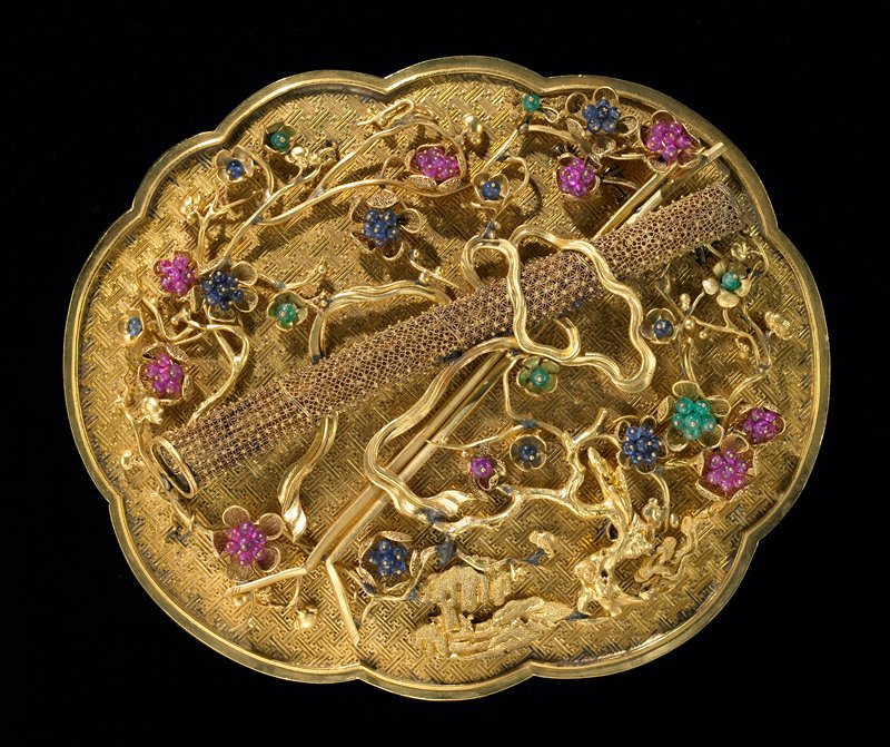 Jeweled gold presentation box; surface chased with swastika fret design and cover bearing filigreed bamboo-tube drum and sticks, emblem of the Taoist philosopher Ch'ang Kuo Lao. The emblem is surrounded with delicately spun gold blossoms picked out with small cabochon rubies, sapphires, and jade. One of a set of eight presented to the emperor Ch'ien Lung in the 43rd year of his reign.