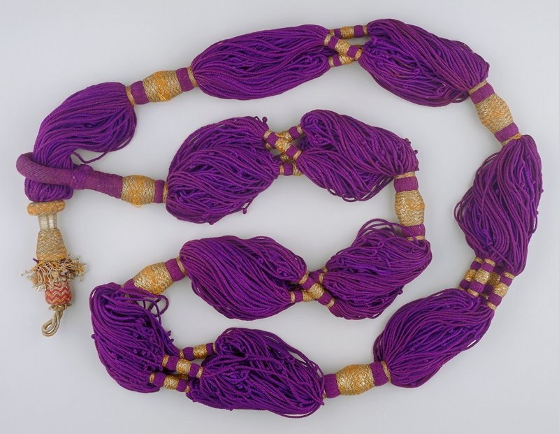 Thin purple silk cords with gold metallic trim twisted around sections in various designs with metallic threads and beads at one end