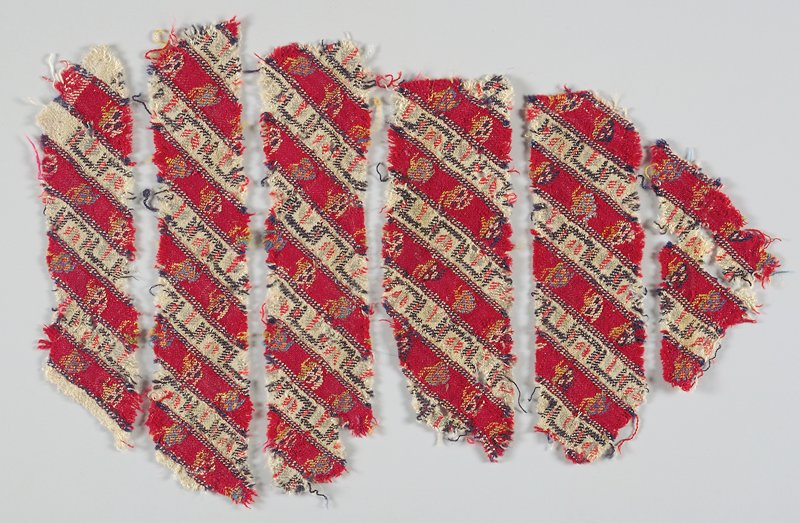 6 separate textile fragments cut on the diagonal from UR to LL; vertical bands of alternating white and maroon; geometric design in blue, green and pink on white bands; floral sprays in white, blue, orange and green on maroon bands. Woven fabric