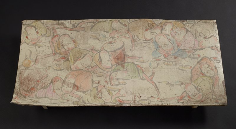 flat rectangular slab platter with two runner legs on underside; top decorated with cartoonish painted image of squatting figures with very tightly placed facial features eating from small bowls; muted pastel colors on cream ground; underside is brown