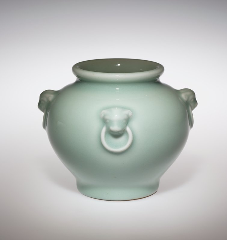celadon green glaze; small ring foot; rounded form with rounded shoulder; ring mouth; four decorative relief Foo dog heads with rings in their mouths (attached to vessel) around shoulder