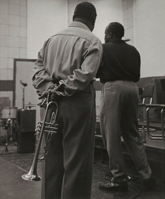 two standing black men seen from back; man in foreground holds a trumpet behind his back