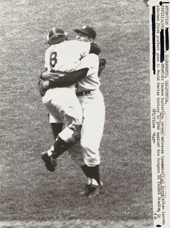 two baseball players hugging; man at left being held off the ground