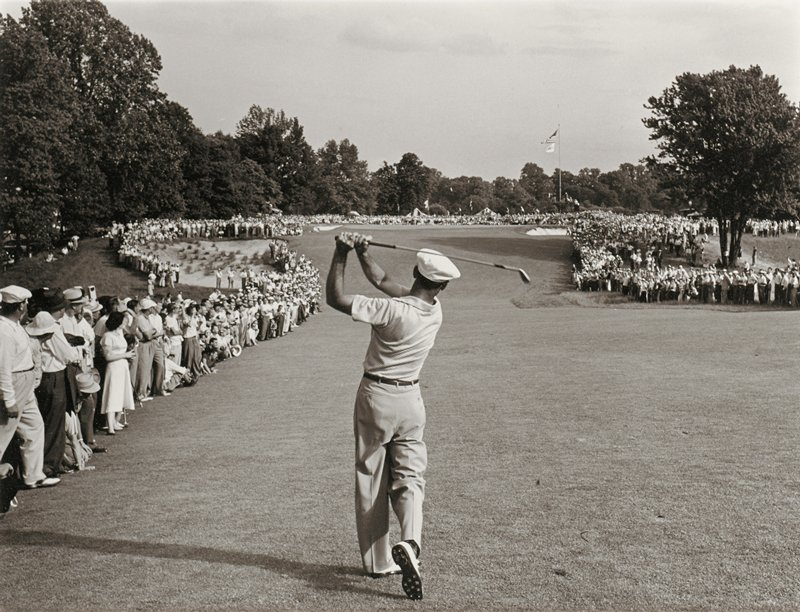 golfer on a golf course, at the top of his swing, seen from back, wearing light-colored short-sleeved shirt, slacks and cap; crowds on course at left and right