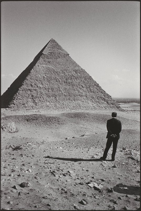 standing man wearing a dark suit, with his hands held behind him, in LRQ, looking a pyramid