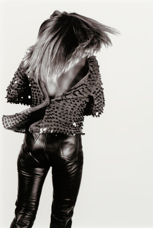 woman seen from back against white ground, tossing her long hair; woman wears a sequined sweater, open at top exposing her back, and black leather pants
