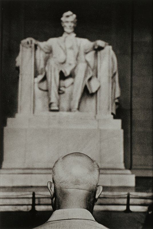 back of head of balding man at bottom center with Lincoln Memorial in background