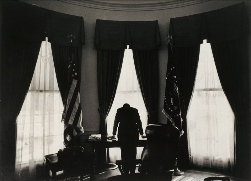 back view of man in silhouette with head lowered, leaning on desk in the Oval Office; three windows with heavy draperies; central window flanked by two flags