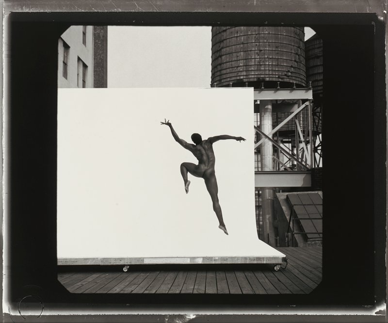 nude black man seen from back leaping, with PL knee and PL arm raised, back twisted and fingers splayed; wheeled white backdrop behind man; parts of buildings and structures (beams, cylindrical elements, walls, skylights) to right and in ULC