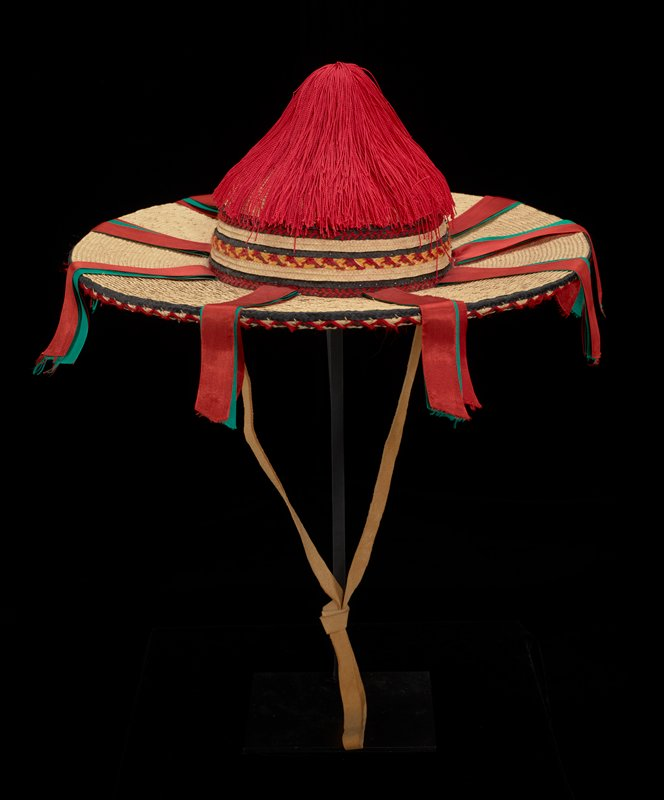 straw hat with wide brim; red tassel at top; red and green ribbons hanging from rim; red and orange-yellow yarn trim; leather chin strap