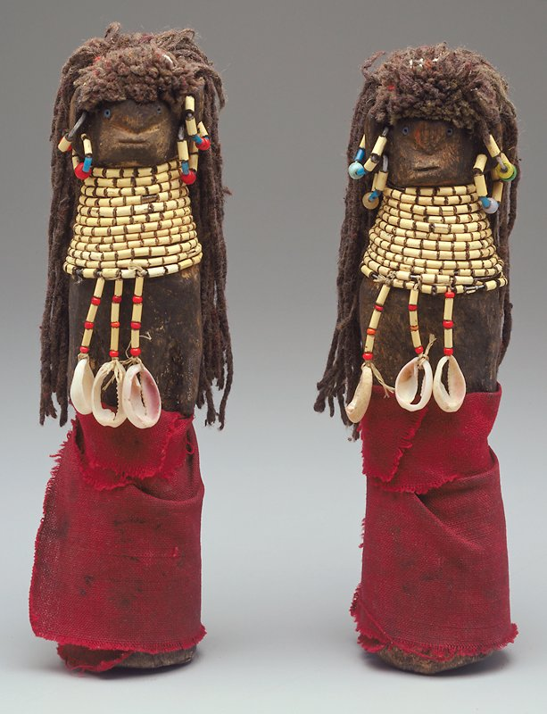 female doll wearing long red cloth skirt, wide coiling strand of beads with three strands extending down in front, each with a shell at the end; two beaded hoop earrings in each ear; long yarn hair