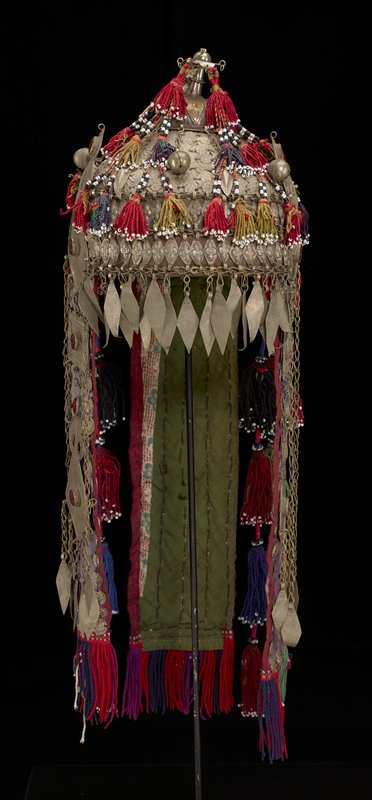 cap with animal hide (?) lining; covered overall on exterior with primarily round hammered discs with floral designs; elaborate metal finial at top with two twisted multicolored yarn tassels at front with black and white beads; triangular multicolored yarn medallion hanging from back of finial, with geometric designs and four yarn and bead tassels on bottom edge; long tail on back of purple silk with green cotton backing, covered on the front with hammered floral medallions; purple, red and blue twisted fringe at bottom edge of back tail; vertical element at each side of head of purple silk (backed with printed cotton with brown and green floral designs) with hammered floral discs, pendant drops and large geometric elements with red glass gemstones; pair of multicolored tassels with beads on each side of hat between side vertical fabric elements and back tail