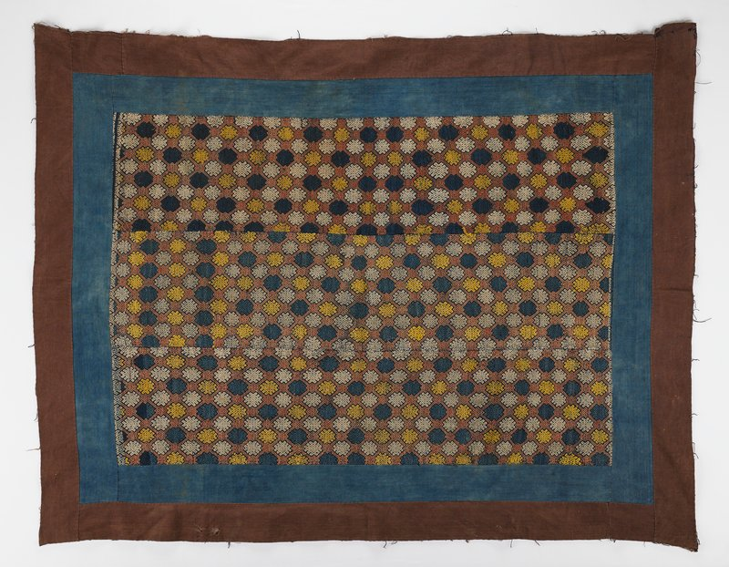 three woven panels sewn together; yellow, blue, white, and rust geometric design; strips of fabric sewn together to form blue inner border and rust outer border