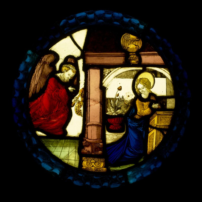 round stained glass panel depicting the Annunciation, with kneeling Mary at prayer at one side and an angel in red at the other side, holding a scroll; white flowers in a vase behind Mary; wave or scroll patterned border