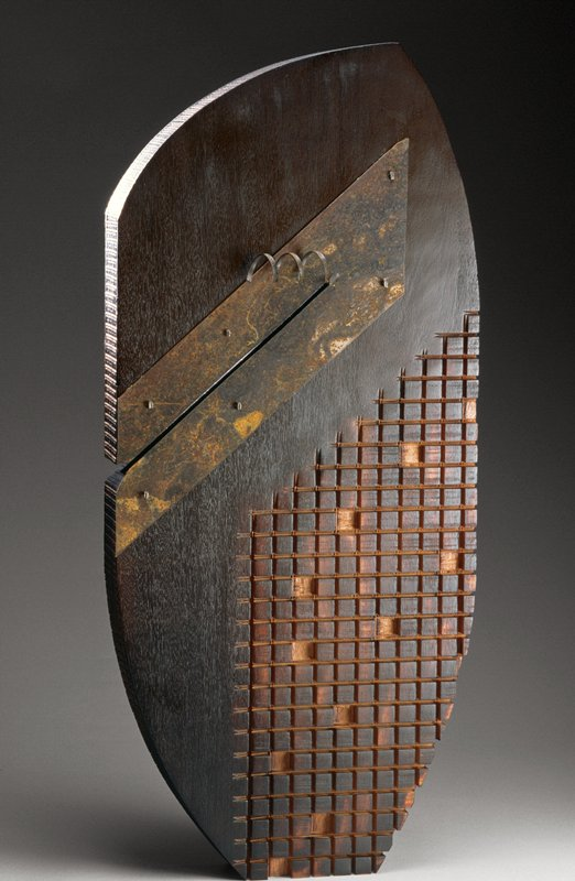 slab with asymmetrical curved top with point at upper right; carved grid pattern with some squared removed in LRQ; diagonal cut in slab at left with slanted U-shaped piece of rusted steel, with slender cut-out at center of piece curled into a spiral; textured incised grid along edges; dark patina with lighter areas at carved areas; textured with diagonal lines on back