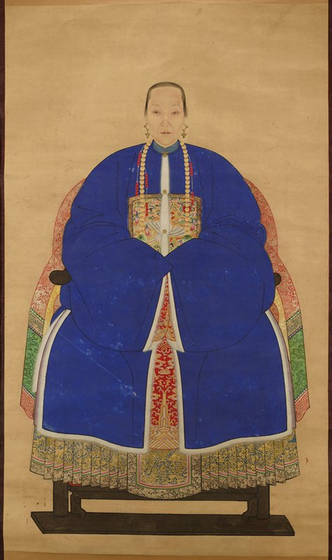 frontal view of seated middle-aged woman wearing blue robe with undergarments with gold dragons; chest piece of gold with white chicken and multicolored clouds or smoke; beads of white, red and jade hang from shoulders; gold earrings with white and red beads