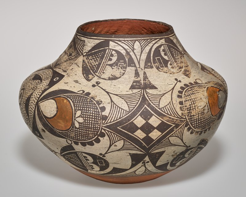squat jar with wide shoulder and inward turning rim on short, wide neck; concave underside; white body with brown geometric and some foliate forms with four red-orange crescent shapes--repeating motifs include checkerboard and teardrop-shaped floriform motif