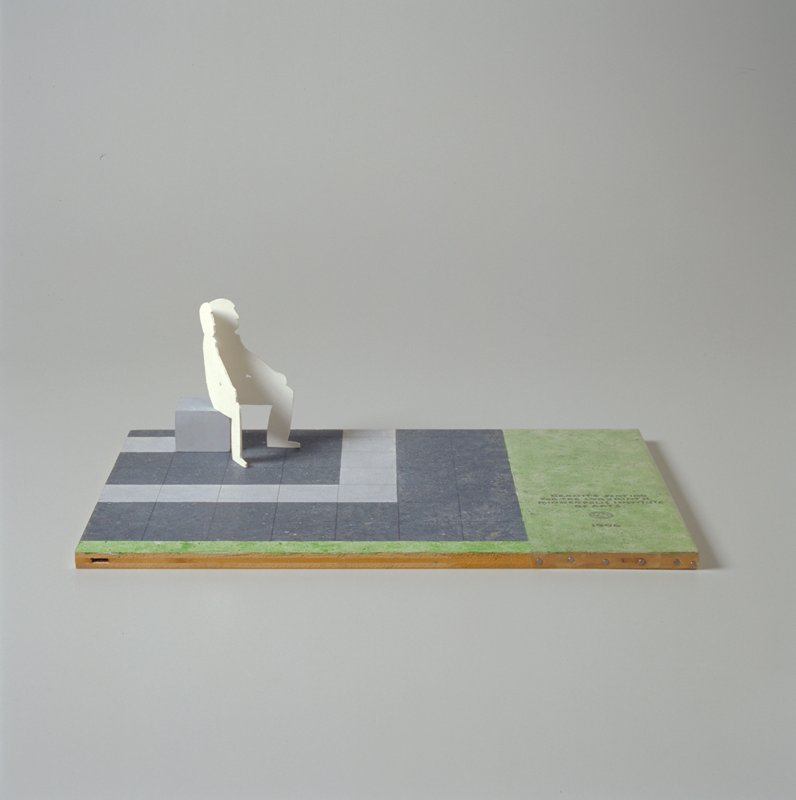Painted base with corner of labyrinth; one square 'bench' at back PR corner; separate cardboard cutout of a male figure can be positioned to sit on bench