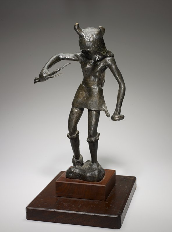 dancing figure looking down, wearing a horned animal skin over his head like a hooded cape; figure wears bells on straps around his knees and holds a rattle in his PL hand and an unidentified arcing object in his PR hand; slightly stylized; attached to two-tiered wooden base