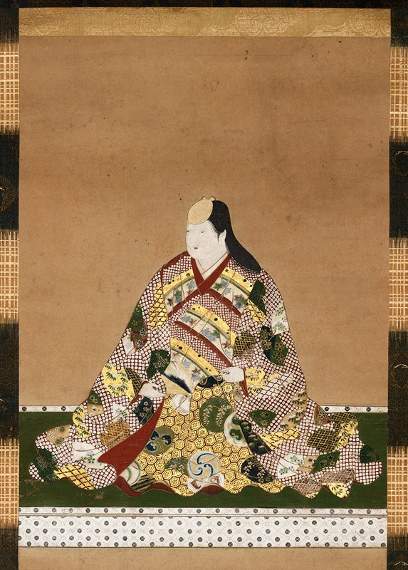 woman seated on a green mat wearing voluminous robes that are richly decorated with heavy patterns in gold, red, white, yellow, and green; gold disc-like head piece over her forehead; she toys with a fan between her hands near lap