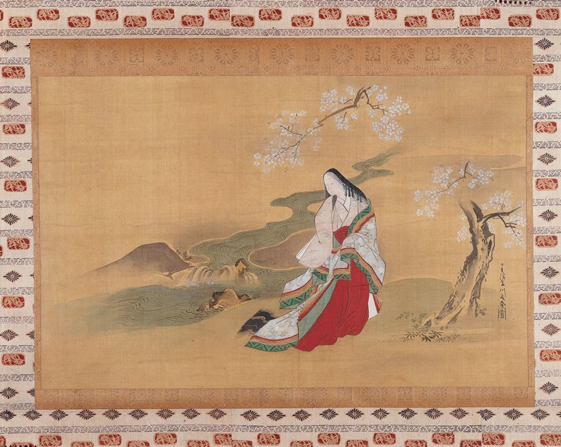 woman standing under a blossoming tree, in front of a winding stream with small cascade; she is wrapped in a large, white kimono with green and red overcoat slipping off shoulder