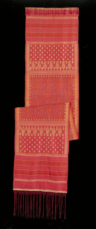 Silk weft ikat; gold thread supplementary weft float design; 2 rows of rickrack trim in gold with knotted red thread trim; maroon ground with orange, blue, green and tan muted swirl designs