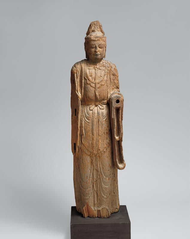 standing wooden figure with shallowly carved draping robes with small tie at waist; peaceful expression on face; long earlobes and squared hat; figure is missing entire PR arm; PL arm is missing below the elbow, but it is apparent arm is bent forward at elbow